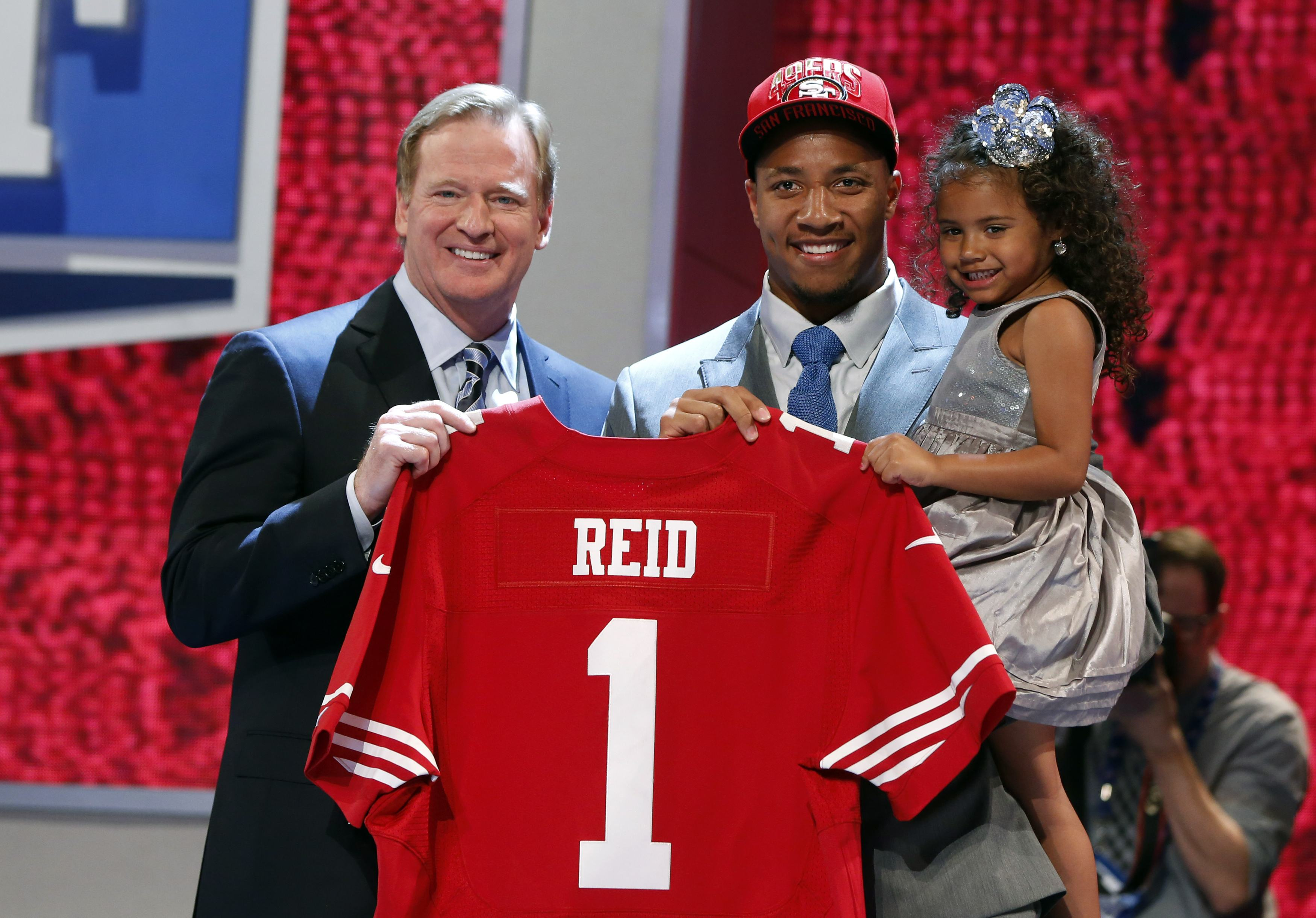 Eric Reid from Louisiana State Uni holds his daughter as he stands on stage with NFL Commissioner Roger Goodell after being selected by the San Francisco 49ers as the 18th overall pick in NFL Draft in New York